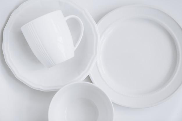 Conjunto de utensílios brancos de três placas diferentes e uma xícara em um prato