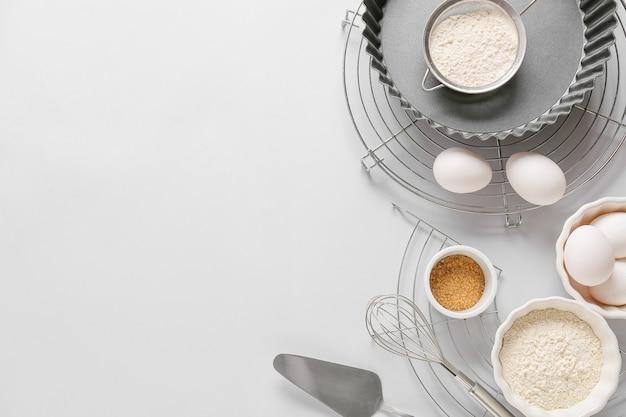 Conjunto de utensílios de cozinha e ingredientes para preparar a padaria em fundo claro