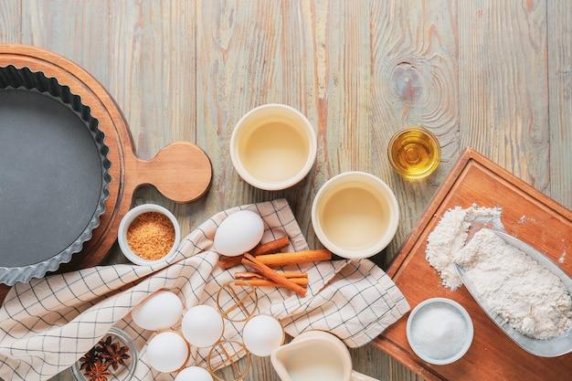 Conjunto de utensílios de cozinha e ingredientes para preparar a padaria em fundo de madeira