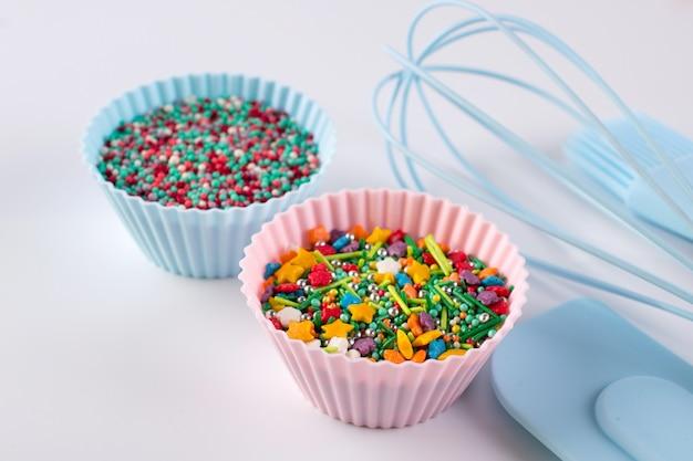 Conjunto de utensílios de cozinha para cozinhar bolos e confeitos de arco-íris para decoração em fundo branco