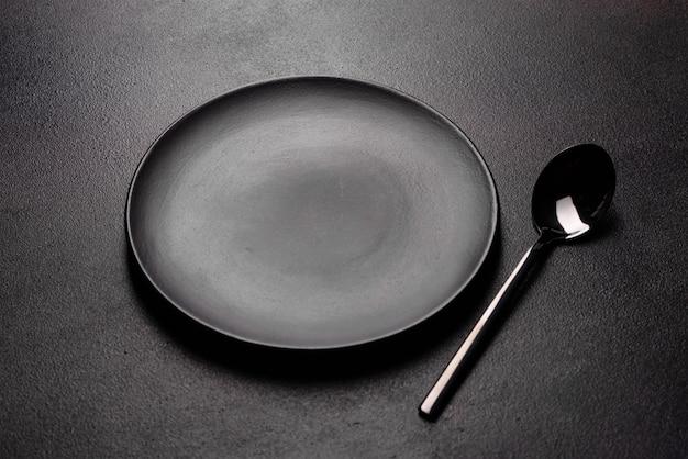Conjunto de utensílios de mesa pronto para a refeição com espaço preto cópia. faca, garfo, colher e prato de metal