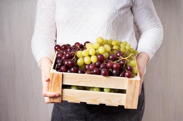 Conjunto de uvas suculentas orgânicas naturais, frutas vermelhas e verdes em caixa de madeira nas mãos de uma garota com roupas leves