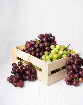 Conjunto de uvas suculentas orgânicas naturais, frutas vermelhas e verdes em caixa de madeira, sobre fundo branco
