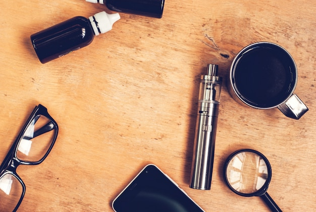 Conjunto de vaping, smartphone e café na mesa de madeira