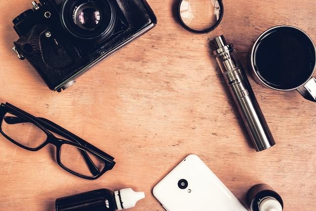 Conjunto de vaping, vintage câmera, smartphone e café na mesa de madeira