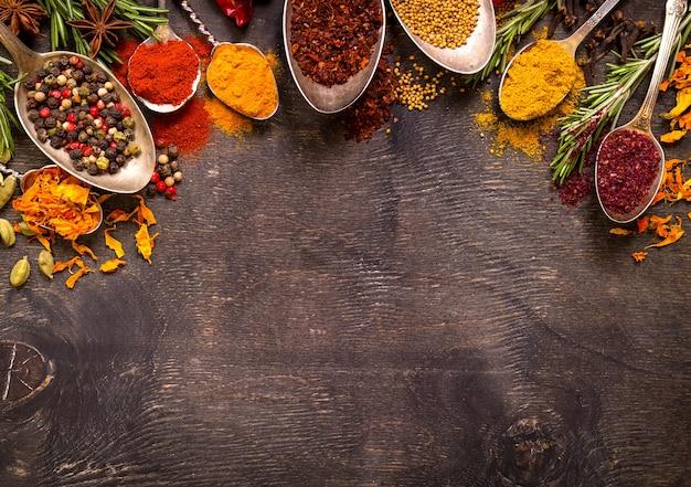 Conjunto de várias especiarias coloridas aromáticas em colheres de vindima velhas e ervas em um fundo escuro de madeira.