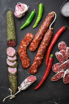 Conjunto de várias fatias espanholas de salame curado a seco e cortes inteiros em fundo preto texturizado, vista superior