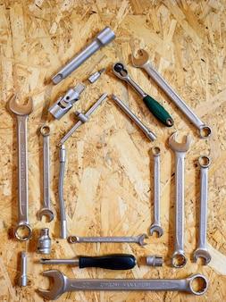 Conjunto de várias ferramentas manuais de reparação ou ferramentas de mecânico de automóveis em forma de casa. kit de ferramentas de reparo. equipamento para construção. fundo de madeira, padrão, vista superior