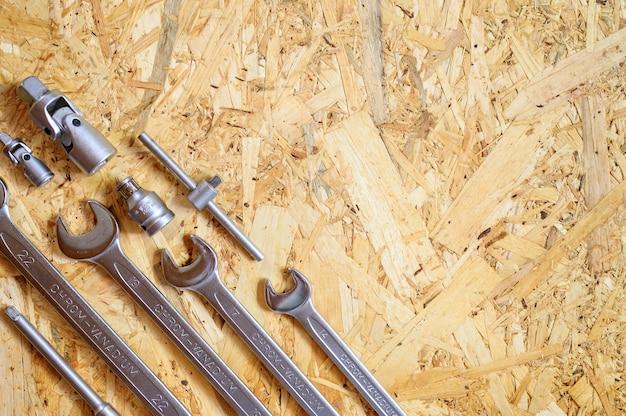 Conjunto de várias ferramentas manuais de reparo ou ferramentas de mecânico de automóveis em fundo de madeira compensada