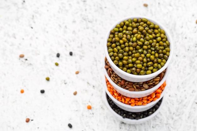 Conjunto de várias variedade de leguminosas indianas em tigelas de melamina branca