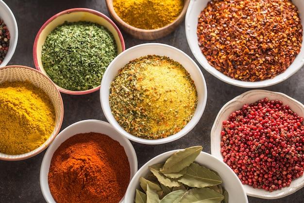 Conjunto de variedade de especiarias e ervas aromáticas em tigelas.