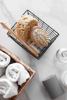 Conjunto de vários acessórios de banho. toalha felpuda, sabonete, pente, óleo, xampu, pano de bucha e velas. a vista do topo