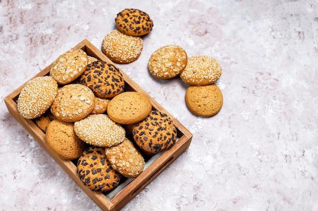 Conjunto de vários biscoitos de estilo americano na bandeja de madeira sobre fundo claro de concreto. biscoito amanteigado com sementes de gergelim, manteiga de amendoim, aveia e biscoitos de chocolate.