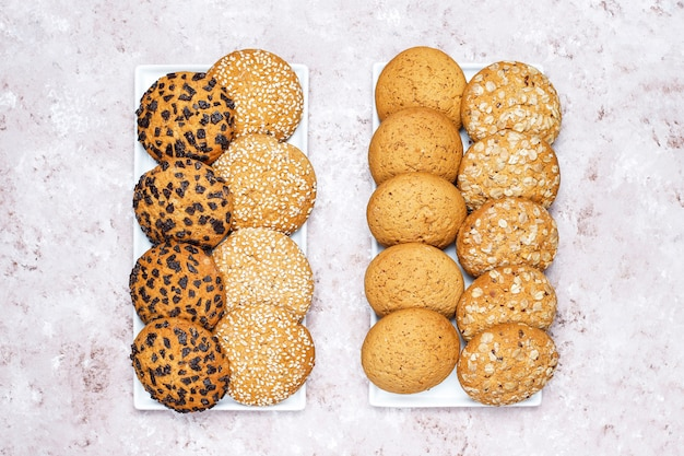 Conjunto de vários biscoitos de estilo americano, sobre um fundo claro e concreto. pão com confetes, sementes de gergelim, manteiga de amendoim, aveia e biscoitos de chocolate.