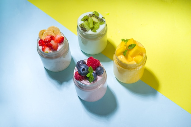 Conjunto de vários iogurtes de frutas e bagas em potes de vidro. variedade de iogurte de café da manhã saudável com mirtilo, morango, manga, kiwi, framboesa, fundo amarelo brilhante moderno com sombras claras e escuras