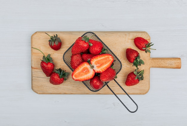 Conjunto de vários morangos ao seu redor e morangos em uma cesta preta sobre uma tábua de madeira e fundo branco. configuração plana.