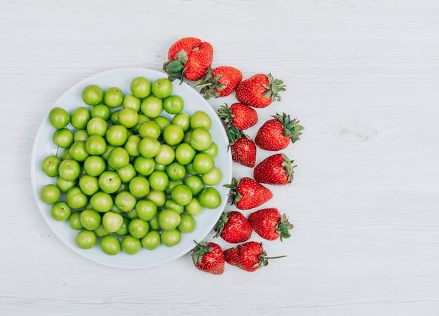 Conjunto de vários morangos e ameixas de cereja verdes em um prato branco sobre um fundo branco de madeira. vista do topo.