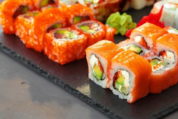 Conjunto de vários rolos de sushi servido em fundo cinza close-up