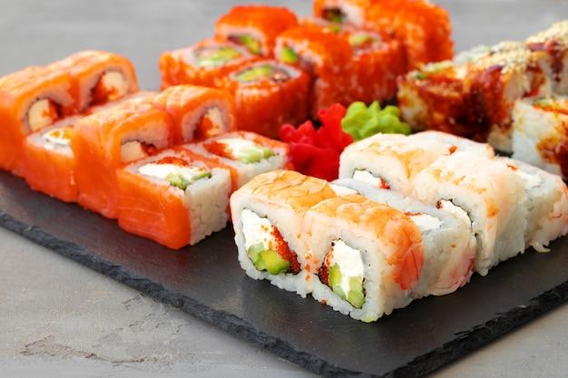 Conjunto de vários rolos de sushi servidos em cinza