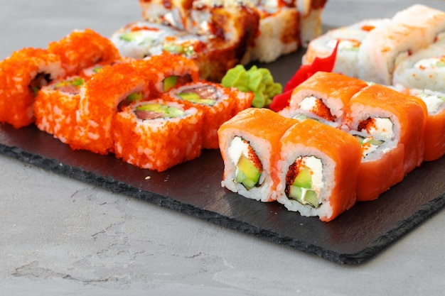 Conjunto de vários rolos de sushi servidos na mesa cinza close-up