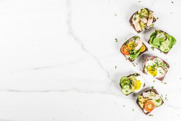 Conjunto de vários sanduíches abertos dinamarqueses smorrebrod com peixe, ovo e legumes frescos