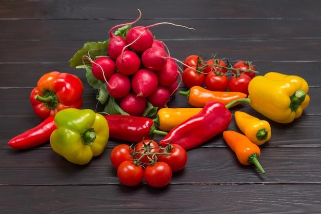 Conjunto de vegetais de pimentão colorido, bando de rabanetes e galhos de tomate vermelho. fundo de madeira escuro. vista do topo