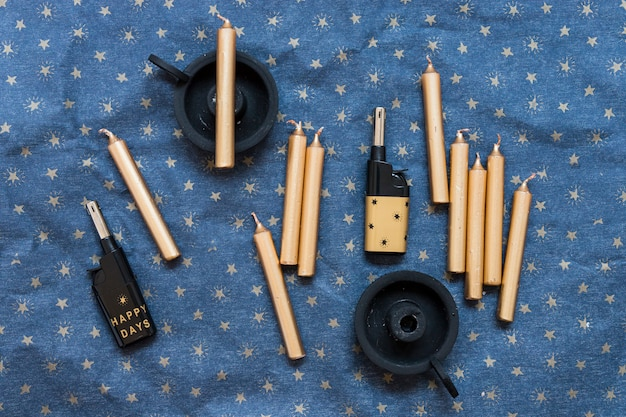 Conjunto de velas perto de castiçais e isqueiros