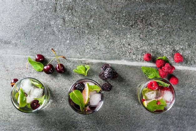 Conjunto de verão tradicional refrescante bebidas berry mojito. com limão, folhas de hortelã, amoras, framboesas e cerejas. com os ingredientes em uma mesa de pedra escura. vista do topo