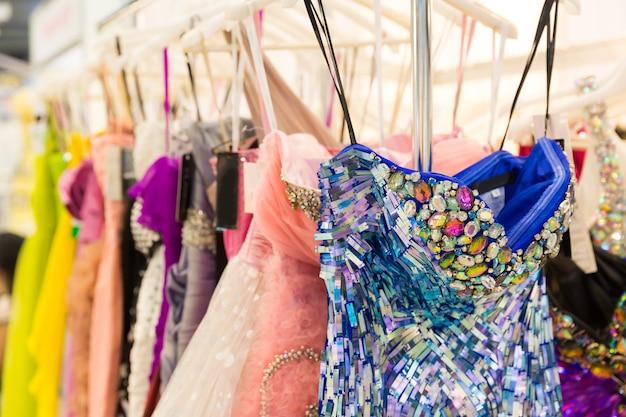 Conjunto de vestidos da moda nos cabides de madeira da loja