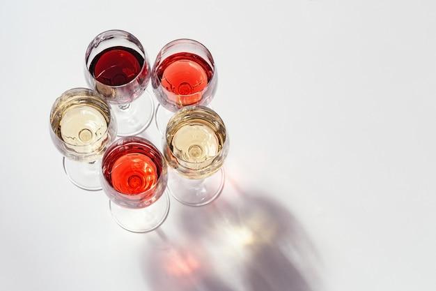 Conjunto de vinho em taças rosa vermelha e vinho branco na mesa de luz vista de cima