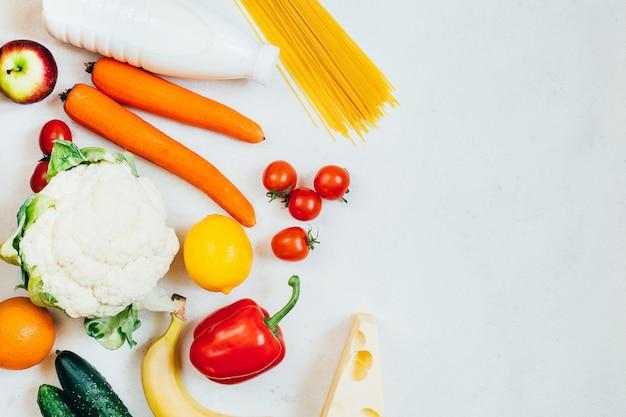 Conjunto de vista superior de alimentos vegetais, frutas e produtos lácteos em fundo branco com espaço livre