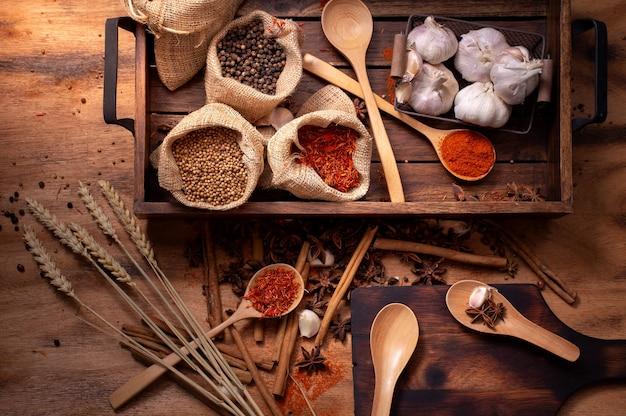 Conjunto de vista superior de especiarias e ervas na bandeja de madeira, alimentos e ingredientes da culinária.