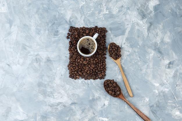 Conjunto de xícara de café e grãos de café em uma colher de madeira sobre um fundo de mármore azul. vista do topo.