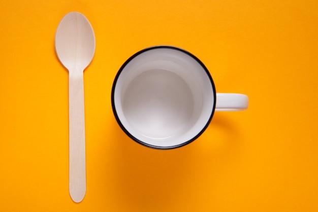 Conjunto de xícara de chá e colher de pau em mesa colorida