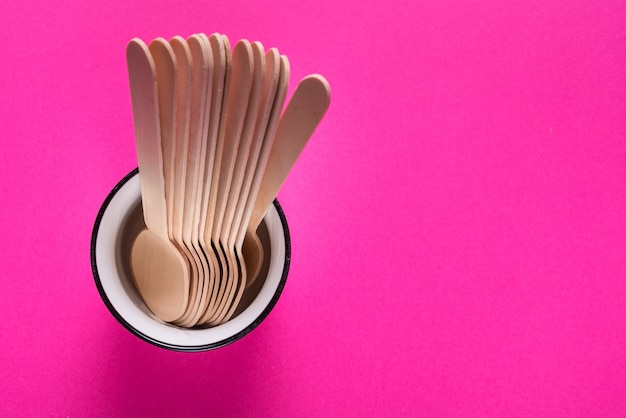Conjunto de xícara de chá e colheres de pau na mesa colorida