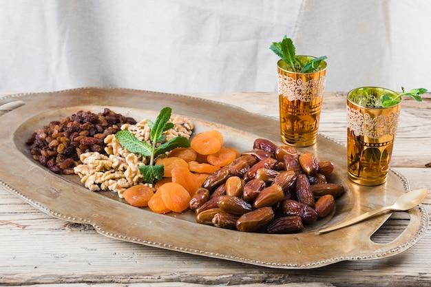 Conjunto de xícaras com galhos de plantas perto de frutos secos e nozes na bandeja na mesa