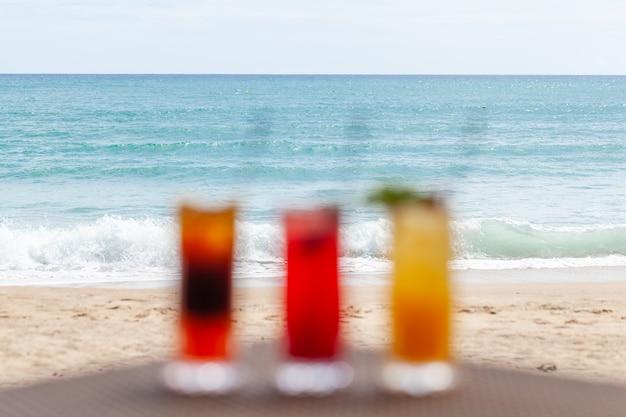 Conjunto desfocado de coquetéis de frutas na mesa na praia com horizonte infinito do mar