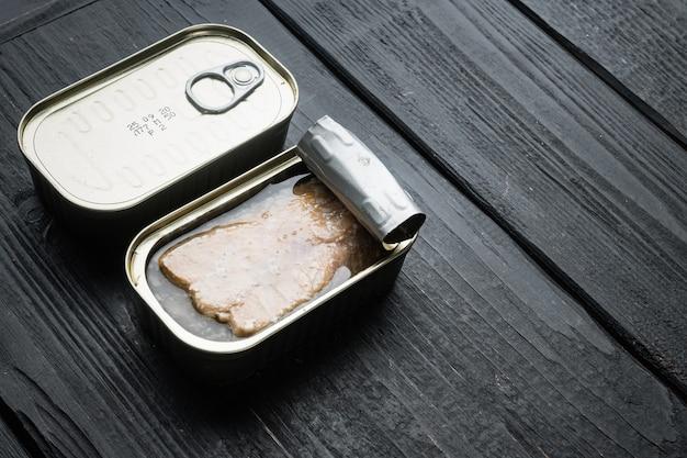 Conjunto enlatado de salmão selvagem do alasca, em lata, na mesa de madeira preta