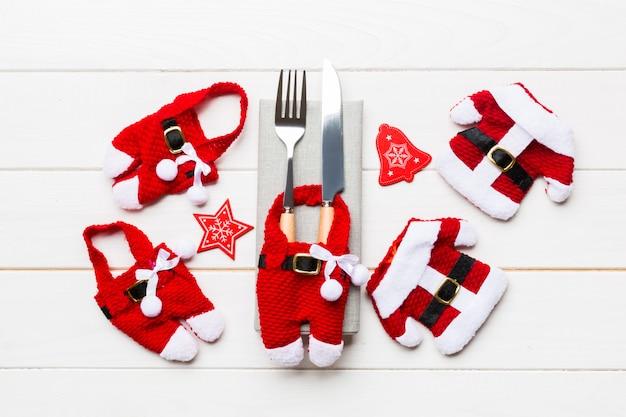 Conjunto festivo de garfo e faca. vista superior de decorações de ano novo e santa roupas e chapéu. feche acima do conceito de natal