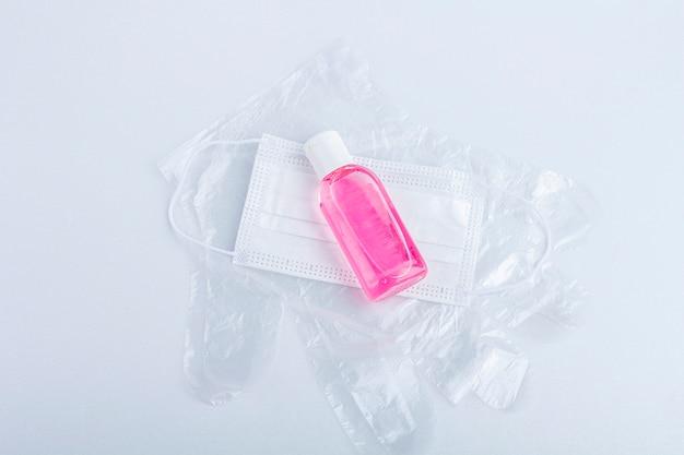 Conjunto higiênico de luvas de plástico descartáveis, frasco com gel desinfetante anti-séptico e máscara médica protetora. produtos de higiene. proteção durante a epidemia de coronavírus.