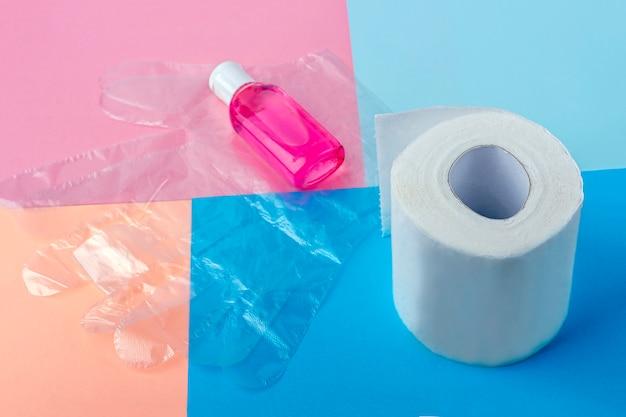 Conjunto higiênico de rolo de papel higiênico, luvas de plástico descartáveis e frasco com gel desinfetante anti-séptico. produtos de higiene. proteção durante a epidemia de coronavírus.
