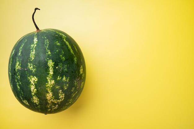 Conjunto inteiro de melancia madura, em fundo de verão com textura amarela, com espaço de cópia para o texto