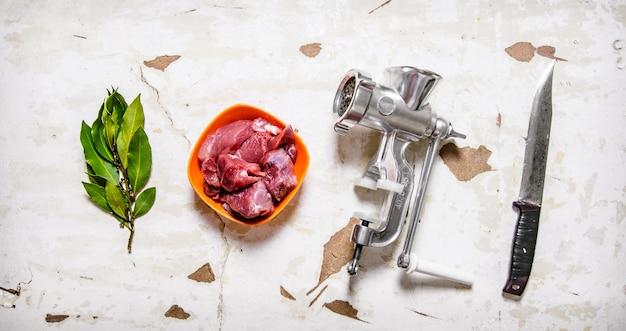 Conjunto - moedor, carne crua, faca de trinchar, folha de louro. na mesa rústica. vista do topo