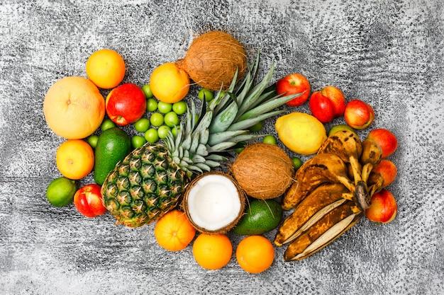 Conjunto multifrutas de bananas, abacaxis, cocos, abacates, marmelos, pêssegos, ameixas verdes, frutas cítricas, vista superior no grunge cinza