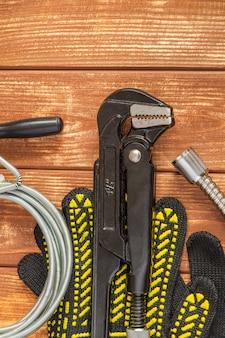 Conjunto necessário de ferramentas e mangueira para o encanador mestre em placas de madeira vintage