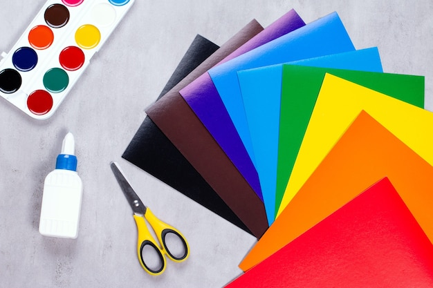 Conjunto para aplicação: papel, cola, tesoura, tintas em um fundo cinza