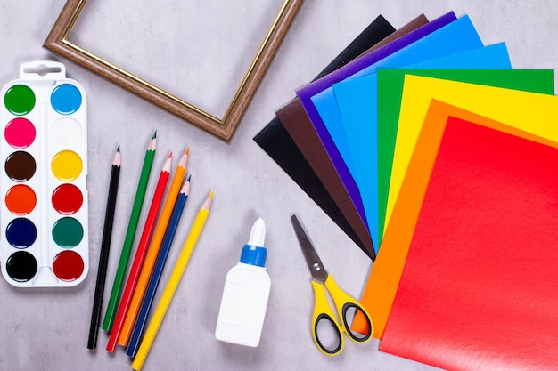 Conjunto para aplicação: papel, cola, tesoura, tintas, moldura em um fundo cinza
