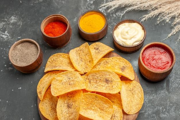 Conjunto para batatas fritas contendo diferentes especiarias, maionese e ketchup na mesa cinza
