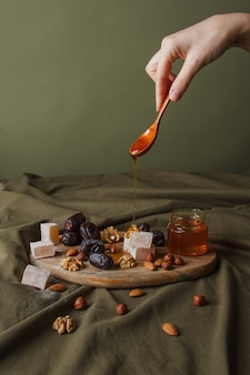 Conjunto para beber chá. mão segurando a colher com mel pingando. vários doces, nozes e mel para chá em uma tábua de madeira. doces saudáveis, sobremesas deliciosas, doces naturais.