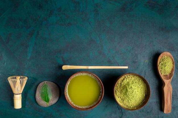 Conjunto para cozinhar chá matcha verde sobre fundo esmeralda. vista do topo.